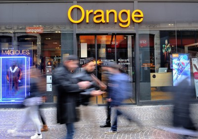 People walk in front of a French telecom operator Orange's store on February 24, 2014 in the French northern city of Lille. AFP PHOTO PHILIPPE HUGUEN